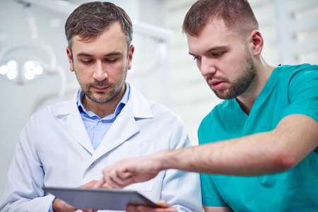 Two caucasian male dentists analyzing x-ray in dental cabinet. Close-up shot