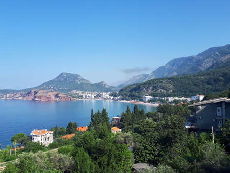View of seafront of Sutomore with trees and buildings, beach with hills and mountains visible in the distance, Montenegro