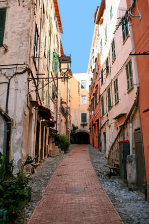 Narrow street made of stone with facades of aged buildings along it in Sanremo, Italy