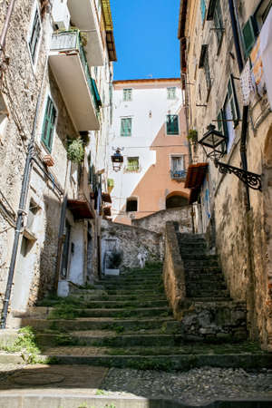 Narrow street made of stone with stairs covered with moss, facades of aged buildings along it in Sanremo, Italy
