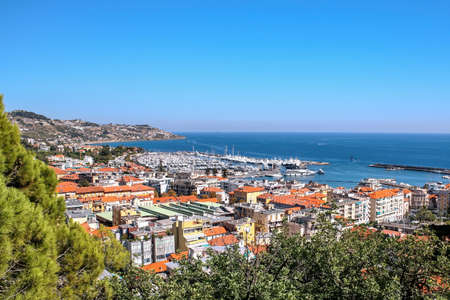 View of Sanremo from a hill with greenery on the foreground, Italy