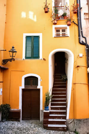 Entrance into an old yellow building in Sanremo, Italy Stock Photo