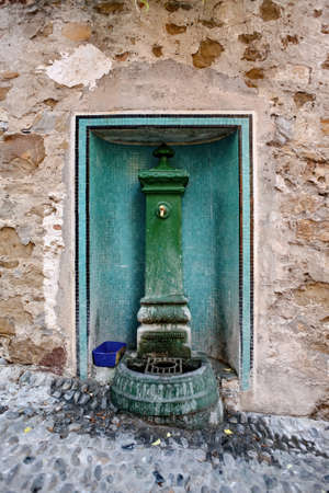 Old drinking water source in a wall in Sanremo, Italy Stock Photo