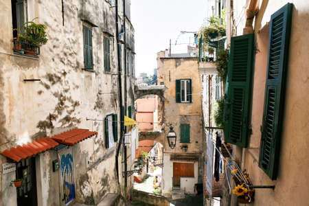 Narrow street with facades of aged buildings along it in Sanremo, Italy