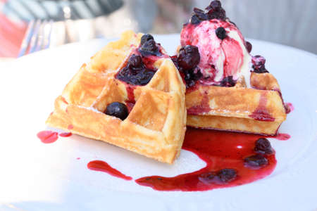 Belgian waffles with ice cream and jam on a restaurant