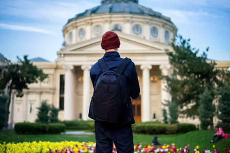 Man with backpack in front of Romanian Athenaeum ATN Academy of Theatre in Bucharest, Romania Zdjęcie Seryjne
