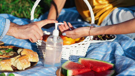 Group of friends at picnic blanket with goodies and disinfectant, in a park during the pandemic in Chisinau, Moldova
