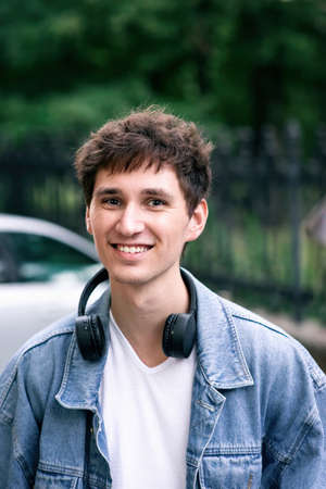 Portrait of a smiling man with brown hair, in white t-shirt and jeans jacket with headphones