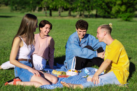 Group of friends having fun at a picnic blanket with goodies, in a park during the pandemic in Chisinau, Moldova