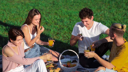 Group of friends eating and drinking, having fun at a picnic blanket with goodies, in a park during the pandemic in Chisinau, Moldova