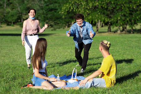 Group of friends having fun at a picnic with goodies on the blanket, in a park during the pandemic in Chisinau, Moldova