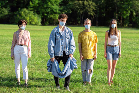 Group of friends in medical masks ready to spread a picnic blanket in a park during the pandemic in Chisinau, Moldova