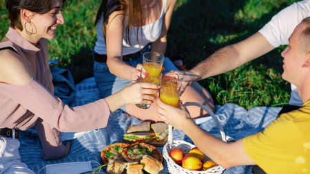 Group of friends clink glasses with juice at a picnic blanket with goodies, in a park during the pandemic in Chisinau, Moldova