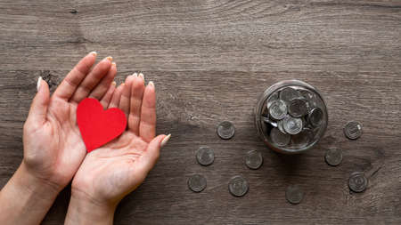 Woman is holding a red hearth, the can with metal coins inside and around it. Woman hands. Wooden background. Top view Imagens