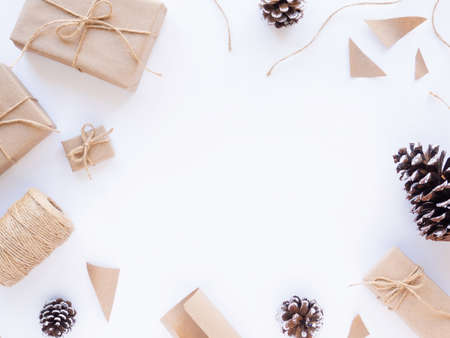 Gift boxes, bits of papers, fir cones, twine. White background. Holiday concept. Top view