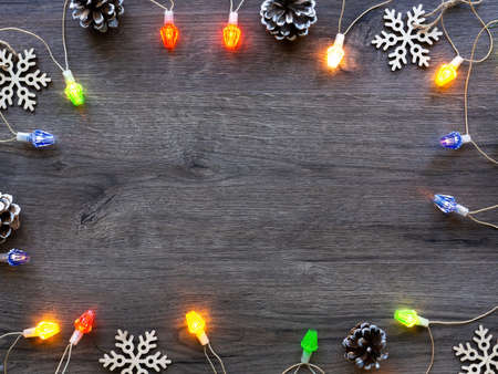 Christmas decorations, fir cones and illumination. Wooden background. Holiday concept. Top view