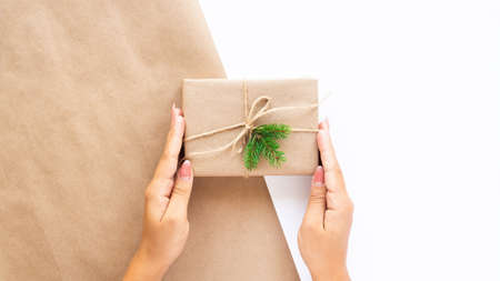 Female hand holds a gift box with a Christmas tree branch on two-color background. Holiday concept. Front view