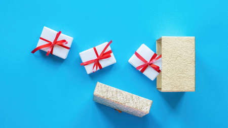 White gift boxes with red tapes and opened box on blue background. Top view