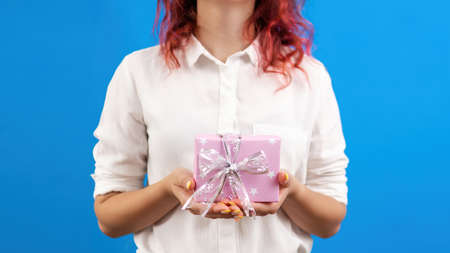 Female holds a gift box on blue background. Holiday concept. Front view Imagens