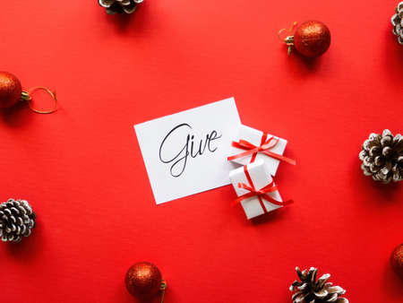Two white gift boxes, note with message and Christmas decoration. Red background. Holiday concept