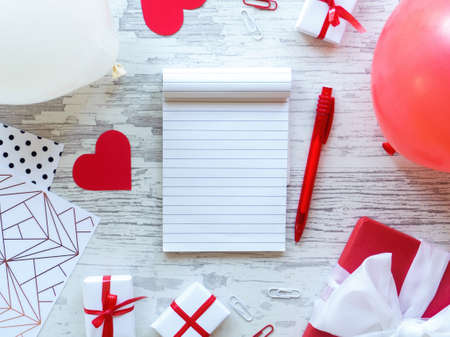 Table with gift boxes, note book, stationery, red hearts, balloons. Love letter concept. Top view Imagens