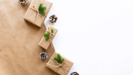 Gift boxes with Christmas tree branches and fir cones on two-color background. Pink and white colors. Holiday concept. Top view Imagens