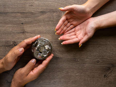 Man giving a woman the can with metal coins, people hands. Wooden background. Top view