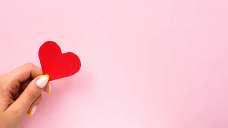 Female hands hold a red heart on pink background. Holiday concept. Front view