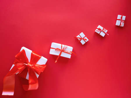 Multiple white gift boxes with red tapes on wooden background. Top view Imagens