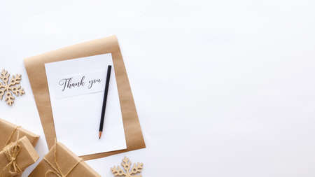 Gift boxes, decoration, notebook with a message and a pencil. White background. Holiday concept. Top view Imagens