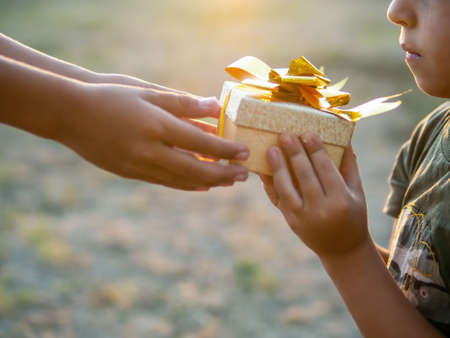 A boy is giving a kid a gift box with golden tape, setting sun. Holiday concept Imagens