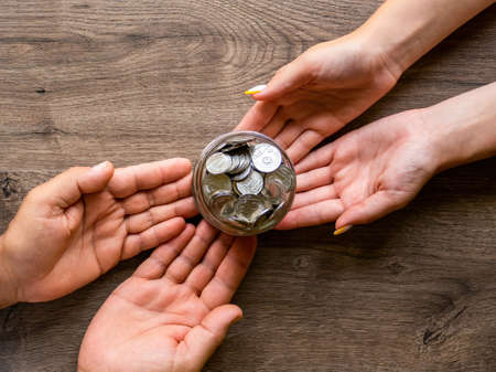 Transfer of the can with metal coins from man to woman , people hands. Wooden background. Top view Imagens