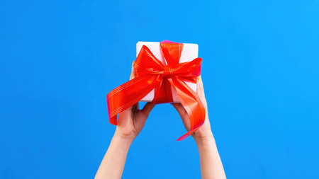 Female hands hold a gift box with red tape on blue background. Holiday concept. Front view