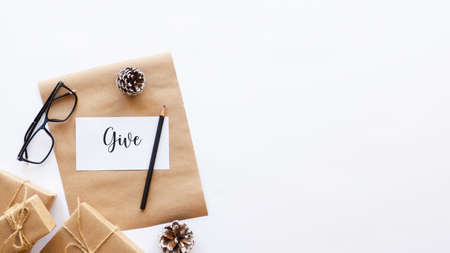 Gift boxes, fir cones, note with a message and a pencil, glasses. White background. Holiday concept. Top view