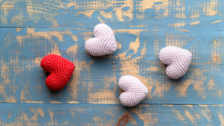 Handmade knitted one red and three pink hearts. Top view