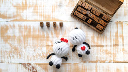 Two handmade knitted toys and wooden set of letters composing word. Top view