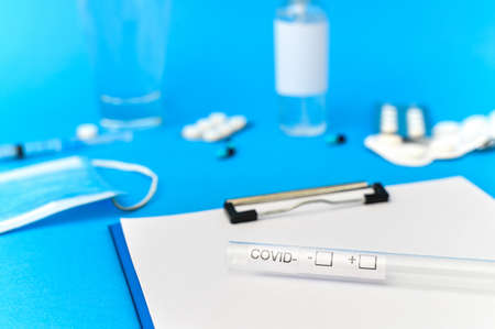 Medical supplies, notepad and covid test composition on blue background. Top view