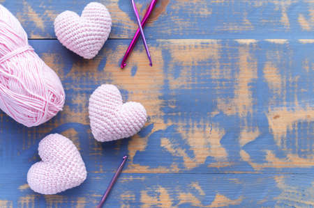 Handmade knitted three pink hearts with ball of yarn. Top view