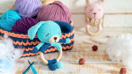 Cute knitted plush toy and multicolored balls of yarn in the knitted couch with plush around them