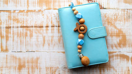 Handmade wooden decoration on the blue wallet. Top view Reklamní fotografie