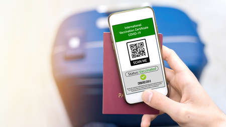 Male hand holding passport and smartphone with International Vaccination Certificate COVID-19 QR code, suitcase Stockfoto