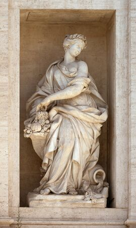 Statue of Abundance of Fruits with a horn of plenty. Detail of the Trevi fountain, Rome, Italy