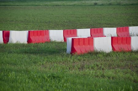 some white and red barriers in a green photo