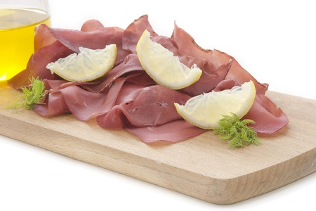 italian cold cuts called Bresaola in white background similar to waves and little lemon ships photo