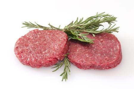 minced beef: some raw hamburgers isolated on white background
