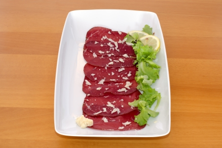 Bresaola with rocket cheese, green salad  and lemon on wooden table Stock Photo