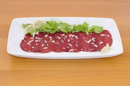 Bresaola with rocket cheese, green salad  and lemon on wooden table photo