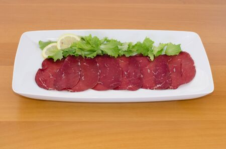 Bresaola with  lemon and green salad on wooden table photo