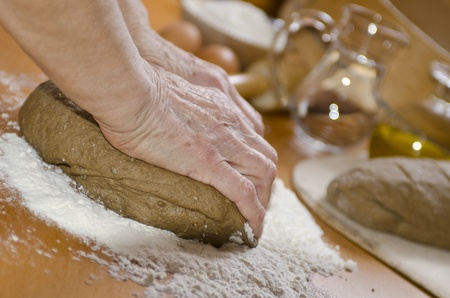 Kneading the Dough at home on wooden table photo