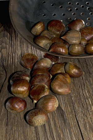 roasting chestnut in a typical italian pan on wooden table photo